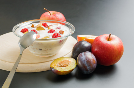 Yogurt with fruits. Glass bowl filled with yogurt mixed with fruit pieces arranged on wooden board with spoon and some apples and plums around on neutral background.