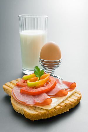 Breakfast. Fresh pork tenderloin sandwich with cheese tomato pepper and parsley arranged with boiled egg placed in a metal stand and glass of milk on neutral gray gradient background. Stock Photo