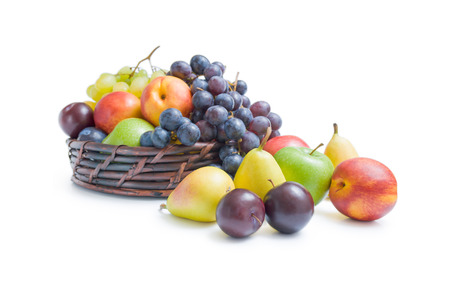 Fruits arrangement. Mix of various fresh ripe fruits plums apples pears peaches and grapes  placed in a wicker basket and around isolated on a white background. Stock Photo