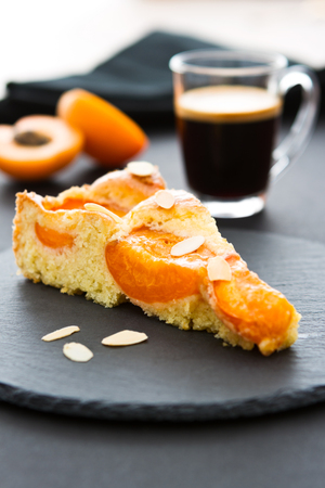 A piece of apricot cake on a black slate, two halves of an apricot, a cup of espresso and a black napkin in the background