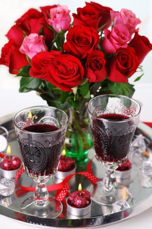 bouquet of roses with red wine and candles. photo