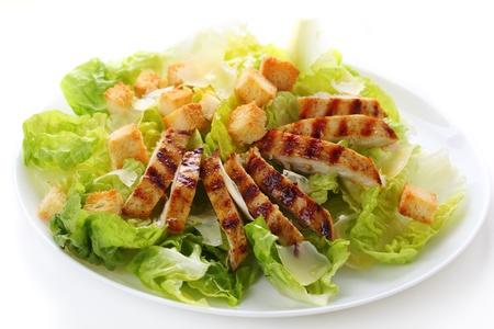 Ensalada César con pollo a la parrilla en un plato blanco.