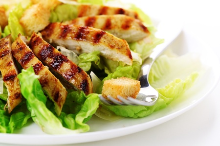 Caesar Salad with grilled chicken on white plate. Stock Photo