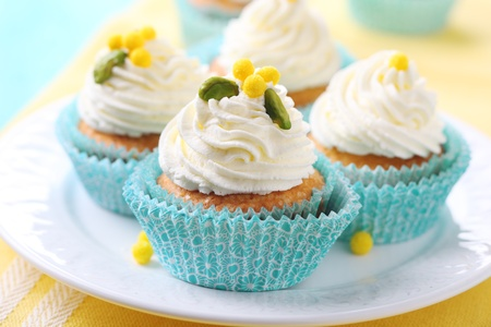 cake stand: Beautiful cupcakes with cream and sugar decoration.