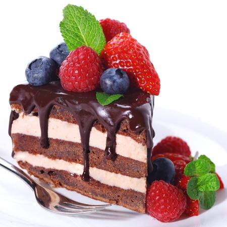 trozo de pastel: Pedazo de pastel de chocolate con bayas frescas y hielo sobre fondo blanco aisladas Foto de archivo
