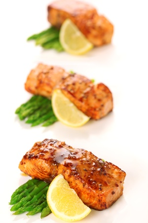 Salmon with honey mustard marinade and asparagus on white background. photo