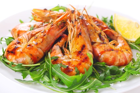 grilled shrimps with lemon on white plate