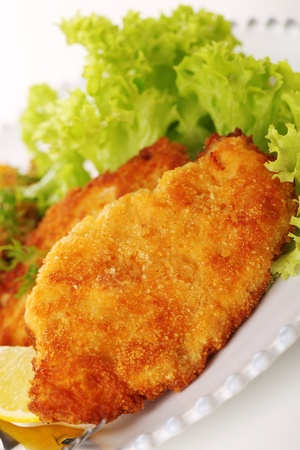 breaded: Wiener Schnitzel on white plate close up
