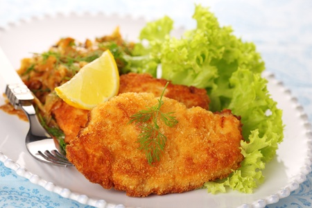 breaded: Wiener Schnitzel on white plate with salad and lemon.