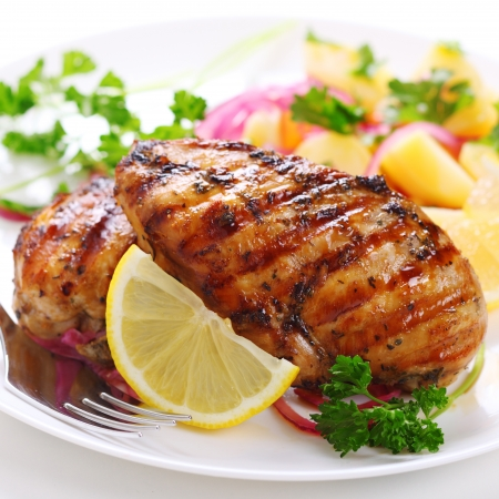 Grilled chicken on white plate Imagens