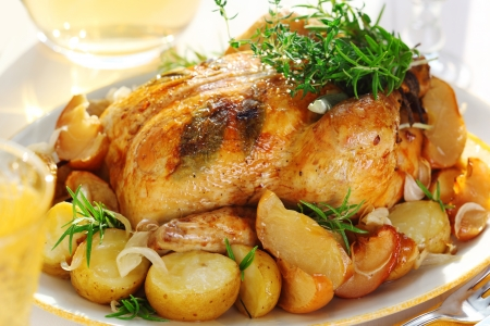pollo asado: Pollo asado entero con las patatas y las hierbas provenzales