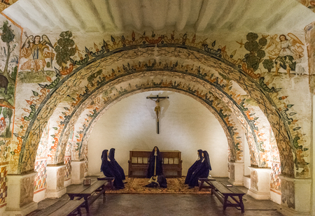 Side chapel with wall 17th century frescoes and Catholic nun mannequins in Santa Catalina Monastery in Cusco, Peru.