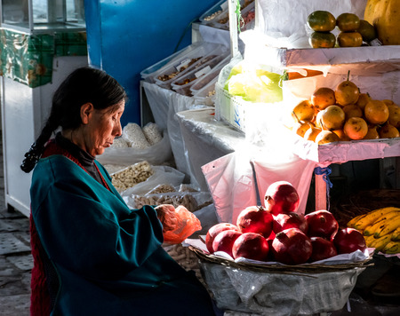 Elderly woman working on preparing produce for sale at the San Pedro market in Cusco, Peru.