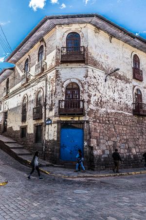 Bright blue door and wood carved balconies in elegant decay in Cusco, Peru.