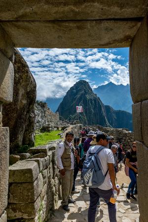 Entering through the doorway at Inca site of Machu Picchu in Peru. Редакционное