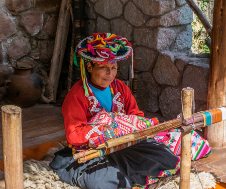 Local village woman making colorful handmade textiles at the Awanacancha Textile site in Peru outside of Cusco. Redactioneel