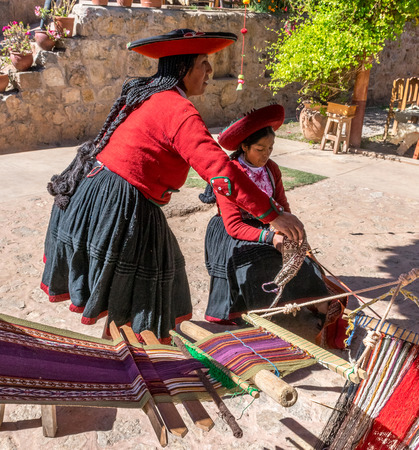 Local village women making colorful handmade textiles at textile site in Chinchero, Peru.