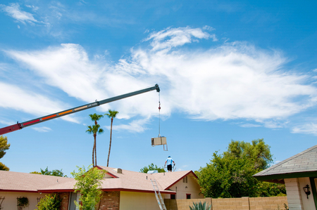 Image of an Air Conditioner being lifted by a crane with a worker