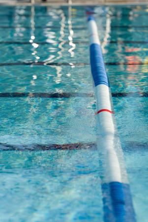 Afbeelding van een rijstrook in een buitenzwembad. Focus gecentreerd op de rode streep op de rij van de rij