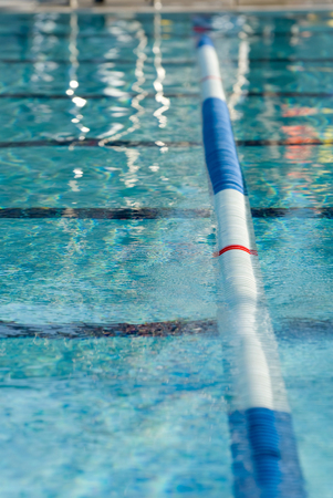 Picture of a lane line in a outdoor swimming pool. Focus centered on the red stripe on the lane line