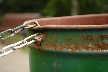 Image of a chained rusted garbage can in a park. Selective focus on where the chain is connected to the garbage can. Lots of space for content.