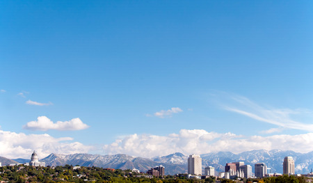 lds: Skyline of Salt Lake City, Utah. Scene includes the Utah State Capitol Building, the downtown skyscrapers and the world famous Mormon Temple with the Wasatch Mountain Range in the background.   Lots of room for type in the image. Stock Photo
