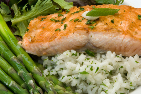 Gourmet Dinner featuring a salmon filet, rice pilaf, asparagus, and mixed greens  Shallow depth of field