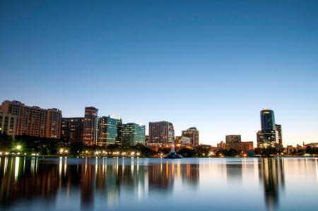 Orlando Florida city skyline at night reflected on Lake Eola. Stock Photo