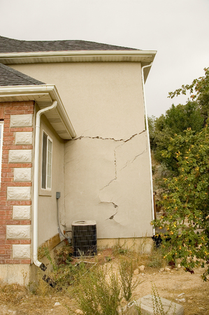 Shifting earth under the foundation of this new home caused major structural damage to the walls, floors, and windows of this beautiful home. Stock Photo