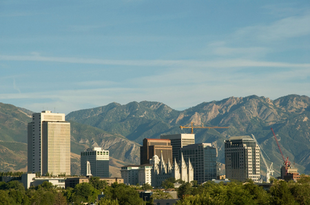 Skyline of Salt Lake City, Utah, with a storm approaching.  The image shows the downtown buildings and skyline, the historic Mormon temple, and the Wasatch mountains in the background.
