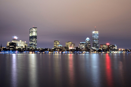 The Boston Massachusetts skyline at night reflected on the water. Imagens