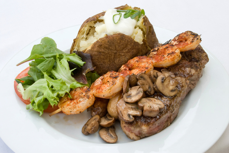 Gourmet dinner of Steak, grilled shrimp, mushrooms, loaded baked potato and mixed greens  Shallow depth of field