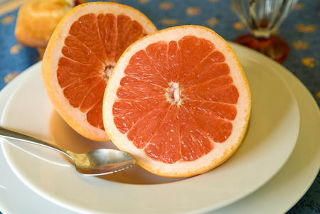 Breakfast of two halves of pink grapefruit.  Shallow depth of field