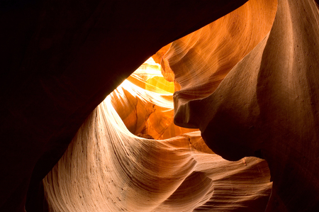 Antelope Canyon canyon curves. Sunlight shining through the curved canyon walls of Antelope Canyon. Plenty of room for copy in the shadows.
