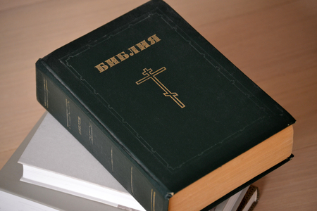 The Bible is dark green in color. Russian language