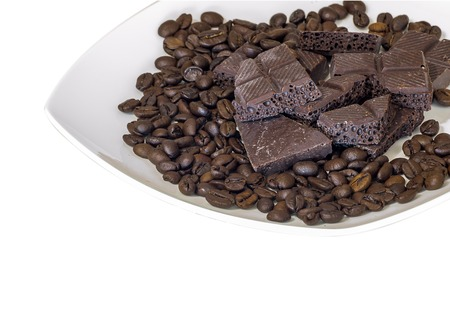Chocolate and coffee beans on a white plate isolated background