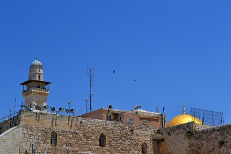 Roofs of churches and the minarets of Jerusalem in the old city on the background of blue sky with two soaring birds