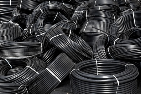 warehouse building: Coiled plastic pipes stored outdoors