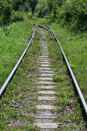 Old abandoned railway overgrown with grass Stock Photo