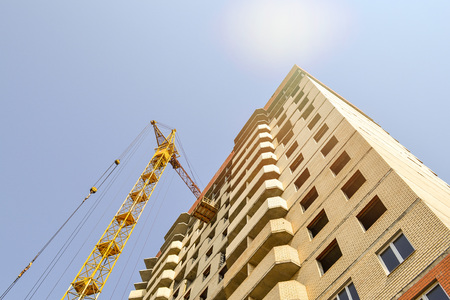 Building crane at the background of a multi-storey building under construction Stock Photo