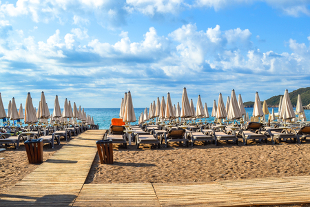 The beach of Montenegro. Sun beds and sun umbrellas in the assembled state on the beach. Clouds over the sea. The Budva Riviera. Vecici