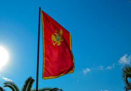Montenegrin red flag with a two-headed eagle, against a blue sky Stock Photo