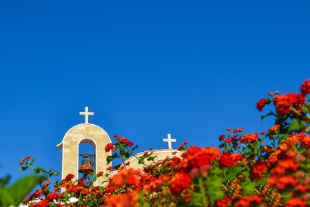 Orthodox church with a tiled roof and a bell. Red roses in the foreground. Cyprus. Ayianapa. Church of St. Epiphany. Stock Photo