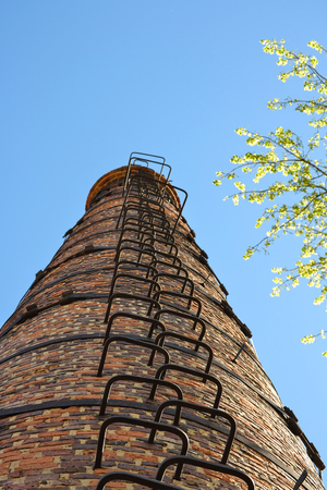 High industrial chimney view from below. Against the background of the sky Stock Photo