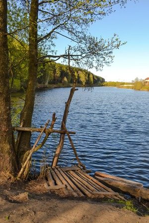 Homemade pier for fishermen from the thick branches on the lake.