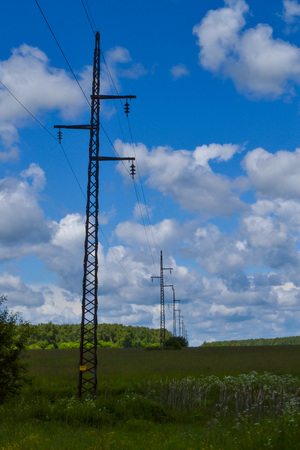 High voltage electrical transmission towers and power lines on field