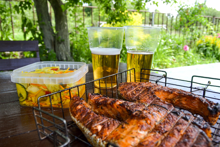 Grilled salmon steak. Two glasses with beer. Cabbage salad. Picnic in nature