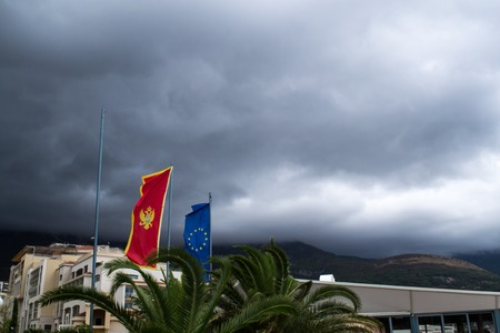 Flags of Montenegro and the European Union against the backdrop of dark clouds. Montenegro. The Budva Riviera Stock Photo