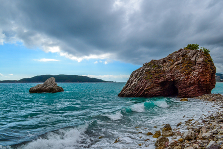 The waves break against the stony shore. The sky is covered with low clouds. Stone islands. Montenegro Stock Photo