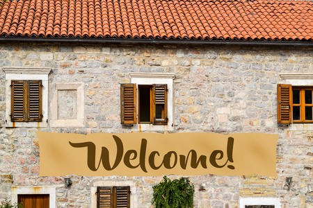 A poster with an inscription is welcome on the facade of an old house with shutters. Europe welcomes refugees Banco de Imagens